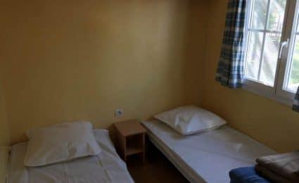 La deuxième chambre du mobile home calvi au camping en Dordogne Périgord Noir dispose de 2 lits simples et de rangements