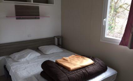La chambre parentale du mobile home Ibiza est équipée d'un grand lit double d'une taille de 160x200 cm et de rangements