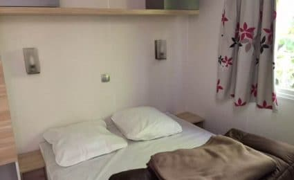 Le chambre parentale du mobile home 834T au camping en Dordogne Périgord Noir est équipée d'un lit double 140x190 cm et dispose de rangements