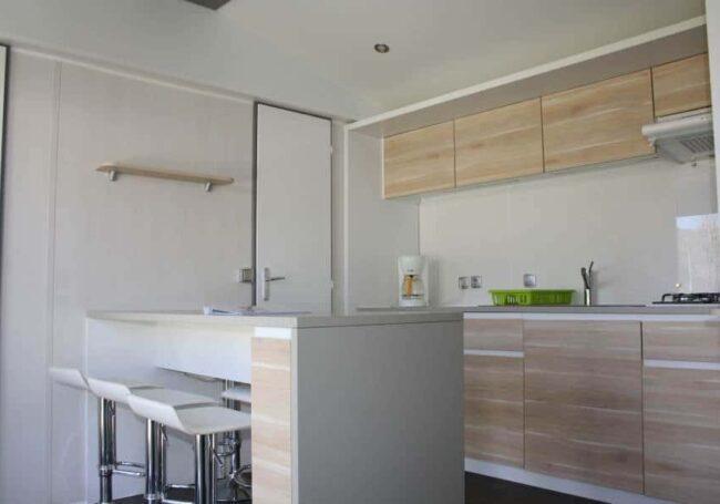 La cuisine du mobile home ohara 884 et équipée d'un îlot central avec 6 chaises hautes pour un maximum de confort