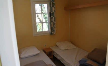 Le mobile home antares dispose d'une seconde chambre équipée de 2 lits simples et de rangements