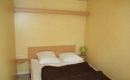 La chambre parentale du mobile home antares est équipée d'un lit 140x190 cm et de plusieurs rangements