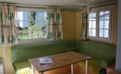 Le salon du mobile home antares est spacieux et confortable. Il est très lumineux grâce à ses grandes fenêtres