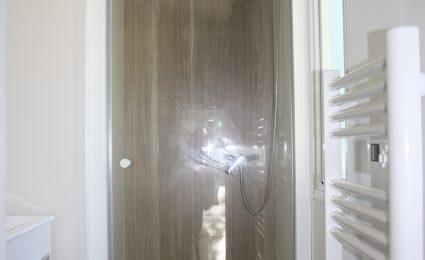 La salle de bain du mobile home bermudes trio est spacieuse. Elle est dotée d'une grande douche et d'un sèche serviette