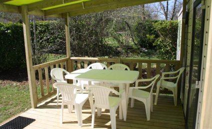 La grande terrasse est couverte. Elle est équipée d'une table avec ses chaises, d'un bain de soleil et d'un fauteuil