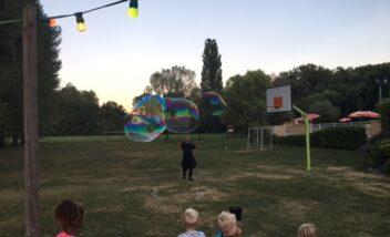 Les enfants participent au spectacle de bulles géantes lors des soirées repas au camping 3 étoiles le Douzou en Dordogne Périgord Noir