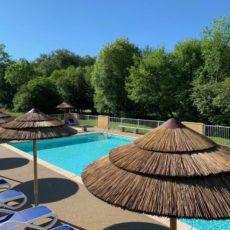piscine chauffée, parasols en roseau, camping dordogne