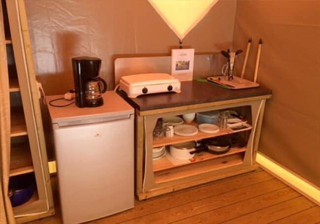 Le coin cuisine de la tente lodge au camping en Dordogne Périgord Noir dispose d'un réfrigérateur, d'une plaque de cuisson au gaz, de la vaisselle et de tous les ustensiles nécessaires