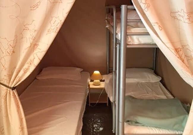 La tente lodge canada est équipée d'une deuxième chambre composé d'un lit simple et de deux lits superposés